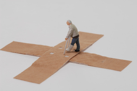 Plastic Figurine Walking With Crutches Over Band-Aids LANG_EVOIMAGES