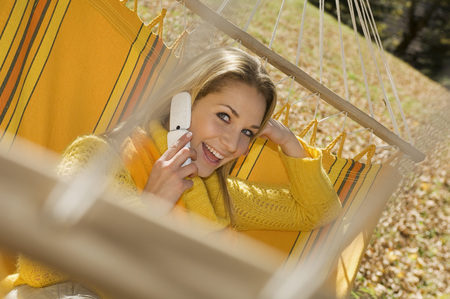 Austria, Salzburger Land, Altenmarkt, Young Woman In Hammock Using Mobile Phone