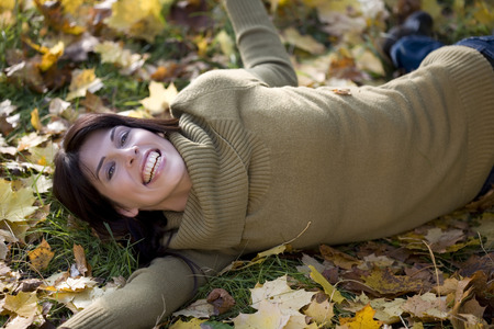 Brunette Woman Relaxing On Autumn Foliage, Portrait