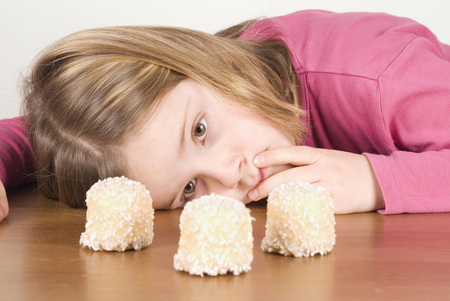 Girl (6-7) Looking At Chocolate Marshmallows, Fooling About LANG_EVOIMAGES