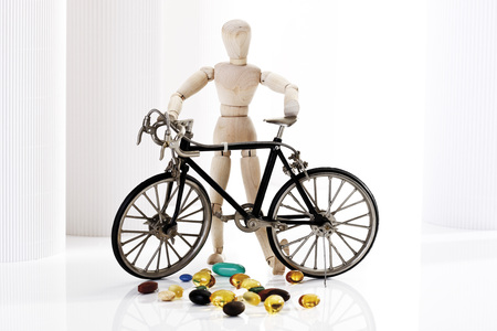 Wooden Figurine Holding Racing Cycle, In Foreground Pills