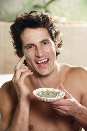 Young Man Applying Facial Mask, Smiling, Portrait LANG_EVOIMAGES