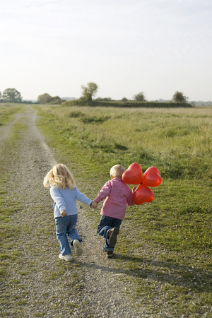 Little Boy And Girl (3-4) With Balloons Running Across Field Path, Rear View