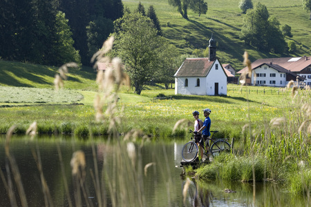 Germany, Bavaria, Allgaeu, Couple With Mountain Bikes Standing On Lakeshore LANG_EVOIMAGES