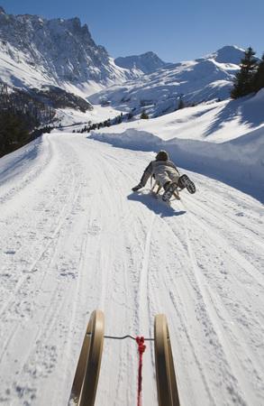 Switzerland, Graubuenden, Savognin, Boy (8-9) Sledging, Rear View