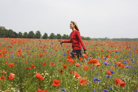 Woman Walking Across Poppy Field