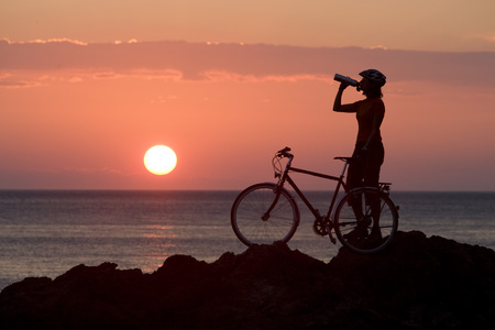 ciclos: Italy, Tuscany, Albegna, Female Mountainbiker Taking A Break At Sunset LANG_EVOIMAGES