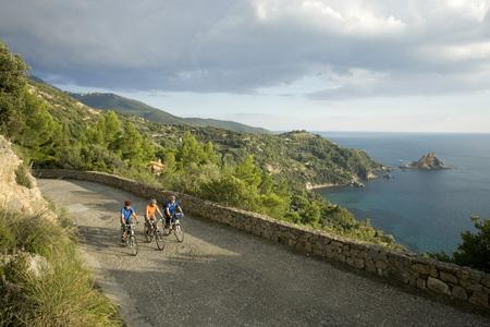 Italy, Tuscany, Monte Argentario, Three Mountainbikers Riding On Coastal Highway