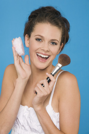 Young Woman Holding Makeup Brush And Powder Puff LANG_EVOIMAGES