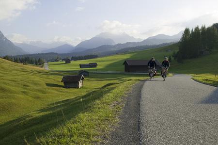 Germany, Bavaria, Mittenwald, Couple Mountain Biking Across Highway