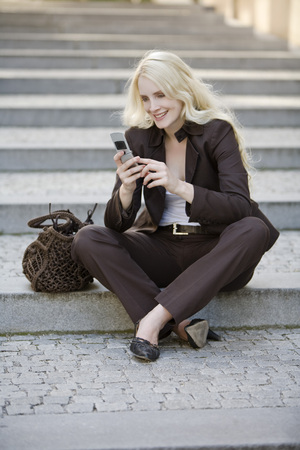 Young Woman Using Mobile Phone, Sitting On Steps, Portrait