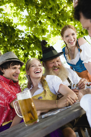 Germany,Bavaria,Upper Bavaria,People Playing Cards In Beer Garden