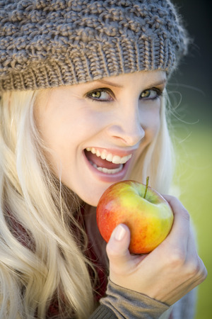 Young Woman Holding An Apple, Smiling, Portrait, Close-Uo LANG_EVOIMAGES