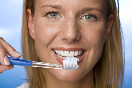 Young Woman Holding Tooth Brush,Smiling,Portrait LANG_EVOIMAGES