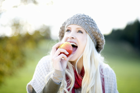 Young Woman Biting Into An Apple, Portrait