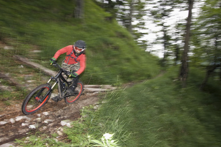 Germany, Bavaria, Chiemgau, Young Man Mountain Biking At High Speed LANG_EVOIMAGES
