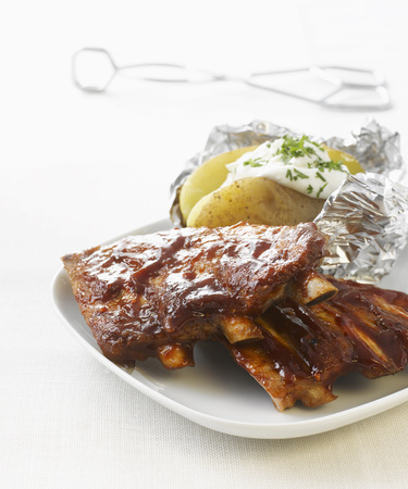 Barbecued Ribs With Baked Potato On Plate