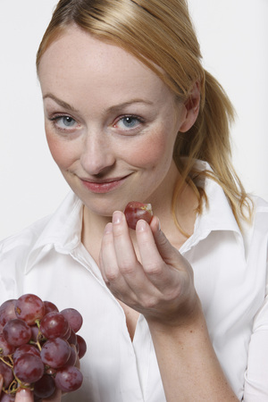Young Woman Holding Grapes, Smiling, Portrait LANG_EVOIMAGES