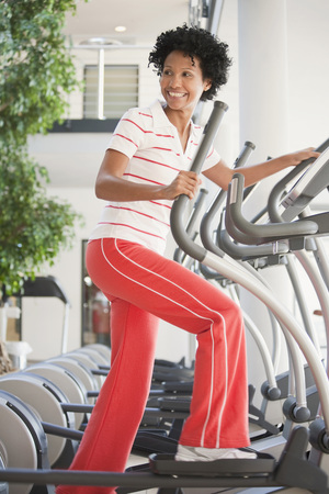 muscle formation: Germany, Bavaria, Woman On Crosstrainer, Smiling LANG_EVOIMAGES
