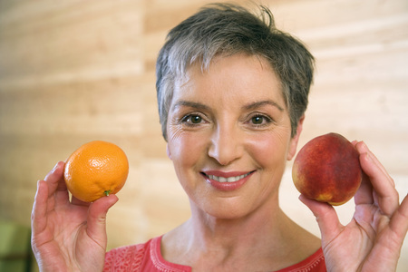 Mature Woman Holding Fruits, Smiling, Portrait