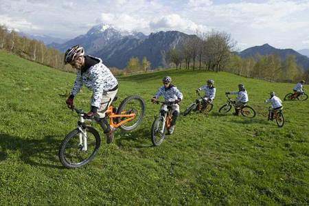Italy, Lake Como, Group Of Mountain Bikers Riding Across Meadow