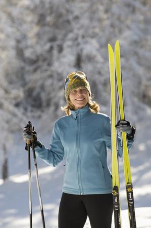 Austria,Tyrol, Seefeld, Wildmoosalm, Woman Holding Cross-Country Skis