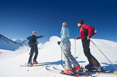 Austria, Salzburger Land, Altenmarkt, Zauchensee, Three Persons Cross Country Skiing In Mountains, Man Pointing With Ski Pole