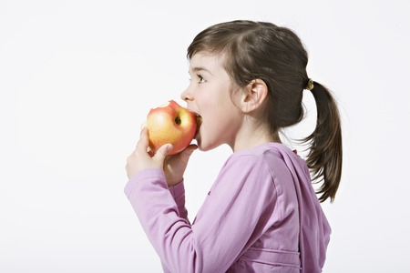 Girl (4-5) Eating An Apple, Side View, Portrait