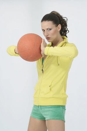 Young Woman In Sports Clothing Holding Basketball