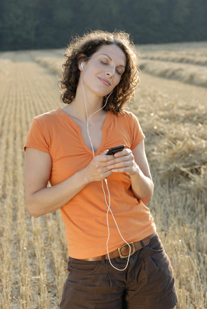 Young Woman In Field Listening To Mp3 Player, Portrait
