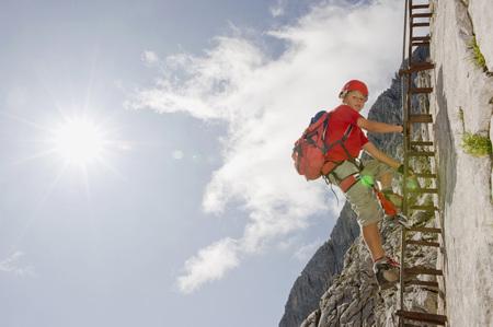 Germany,Garmisch-Partenkirchen,Alpspitz,Boy (12-13) Climbing Rock Face On Ladder,Low Angle View