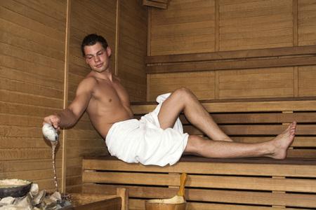 Die Türkei, junger Mann in der Sauna gießt Wasser auf Steinen