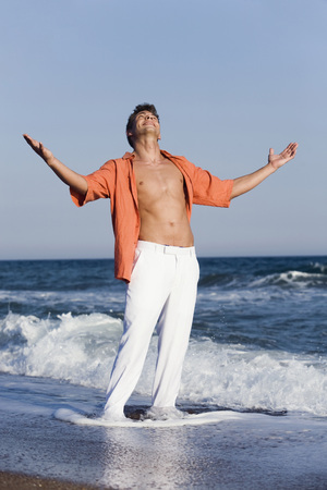 Turkey,Young Man On Beach With Arms Outstretched LANG_EVOIMAGES