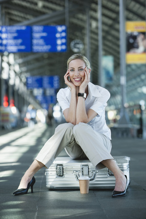 Germany, Leipzig-Halle, Young Woman In Airport Departure Lounge, Sitting On Suitcase