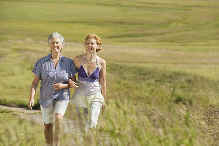 Italy,Seiseralm,Two Women Arm In Arm Walking In Field,Smiling,Portrait LANG_EVOIMAGES