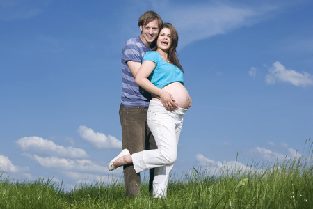 Young Man Embracing Pregnant Woman, Standing In Meadow, Smiling, Portrait LANG_EVOIMAGES