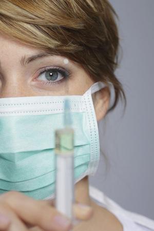 Female Doctor Holding Syringe,Portait,Close-Up LANG_EVOIMAGES