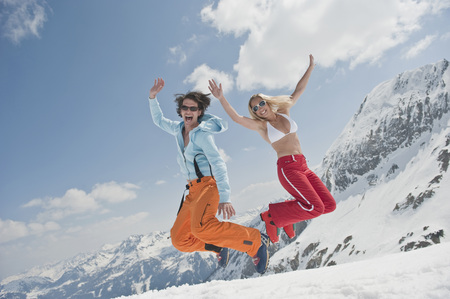 Austria,Salzburger Land,Young Couple Jumping In Air,Laughing,Portrait