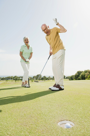 Spain,Mallorca,Senior Couple On Golf Course,Man Cheering