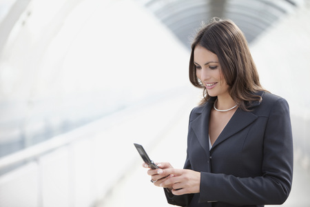 Germany,Bavaria,Munich,Businesswoman Using Mobile Phone At Airport,Portrait