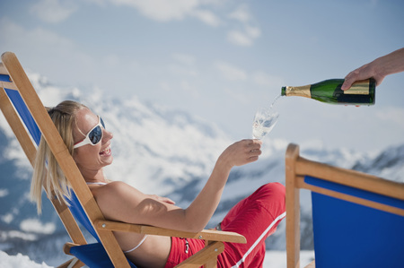 snowcovered: Austria,Salzburger Land,Young Woman In Deck Chair Holding Champagne Glass,Smiling,Portrait