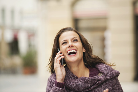 Germany,Bavaria,Munich,Woman Using Mobile Phone,Laughing,Portrait