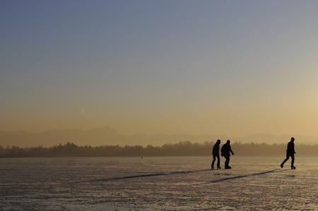 Germany, Bavaria, Lake Starnberg, Silhouettes Of Three People Ice-Skating LANG_EVOIMAGES