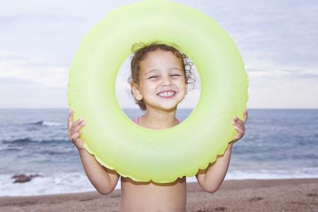 France,Corsica,Girl (2-3) Looking Through Inner Tube,Smiling,Portrait