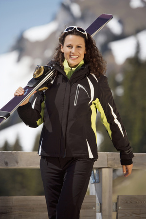 Italy,Alto Adige,Woman Carrying Ski,Smiling,Portrait LANG_EVOIMAGES