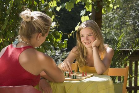 Austria,Salzburger Land,Teenage Girls (14-15) Playing Ludo In Garden LANG_EVOIMAGES