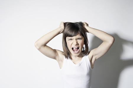 Girl (10-11) Standing Against White Background,Pulling Hair