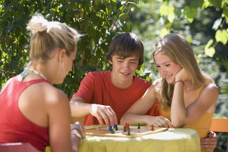 Austria,Salzburger Land,Teenagers (14-15) Playing Ludo In Garden