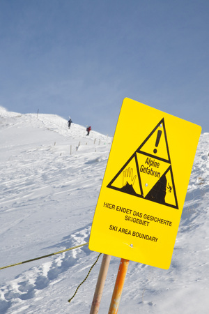 Germany,Bavaria,Warning Sign With People Skiing In Background