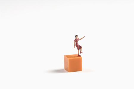 Female Figurine Standing On Building Brick